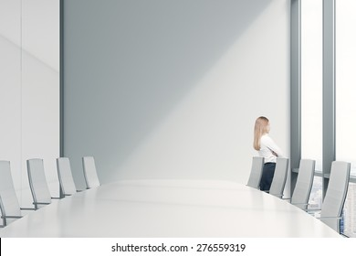 Side view of the young beautiful lady who is looking out the panoramic window in an office. Conference room in a modern office of a consulting company.