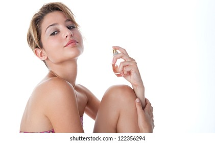 Side view of a young beautiful woman spraying perfume on herself, isolated on a white background.