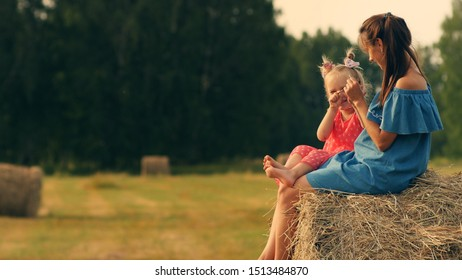 Side view of young beautiful woman play with five years old daughter while sitting on haystack in the meadow at the sunset. Mother and little daughter sitting on haystack on the golden hour.