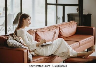 Seitenansicht der jungen schönen Frau, die zu Hause mit Laptop arbeitet.