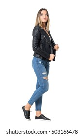 Side view of young beautiful woman in ripped jeans and black jacket looking up. Full body length portrait isolated over studio white background.