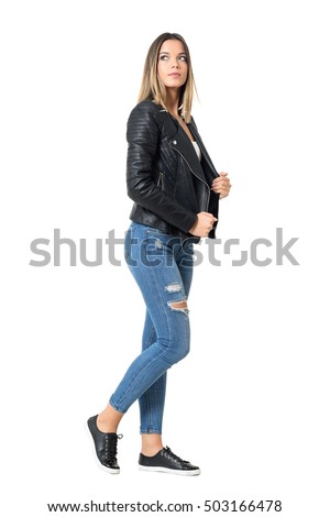 e863cca3d Side view of young beautiful woman in ripped jeans and black jacket looking  up. Full