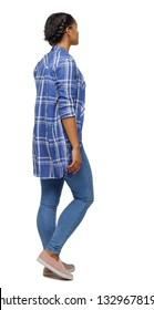 Side view of a young black girl walking in jeans and a checkered shirt. beautiful girl in motion. backside view of person.  Rear view people collection. Isolated over white. A black girl passes by.