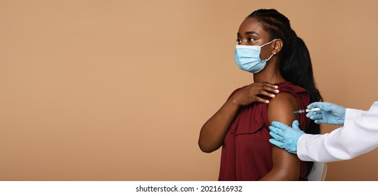 Side view of young black woman patient wearing protective face mask getting vaccination against coronavirus while COVID-19 pandemic, nurse making injection in shoulder, panorama with copy space
