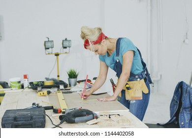 Side view of young blond woman in jeans overalls and tool belt bending over wooden workbench drawing lines with pencil on plywood surrounded by instruments in workshop.