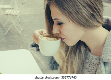 Side view of young blonde woman drinking latte while sitting outdoors in cafe