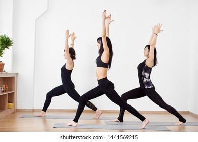 Side view of young brunette female practicing yoga asana with hands up and turning in one direction. Group of people doing yoga in Warrior pose at studio. Fitness, sport, balance and healthy lifestyle