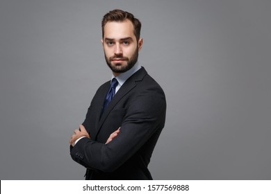 Side view of young business man in classic black suit shirt tie posing isolated on grey background. Achievement career wealth business concept. Mock up copy space. Hold hands crossed, looking camera
