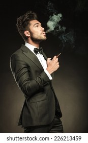 Side view of a young business man blowing smoke while holding a cigarette in his right hand. Looking up, on black studio background.