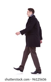 side view of a young business man walking forward on white background