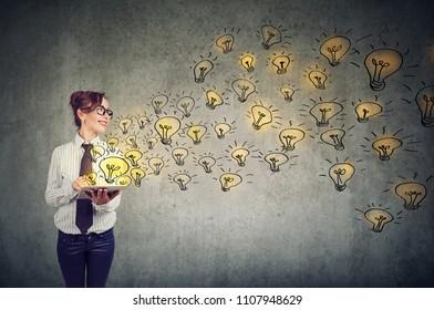 Vue latérale d'une jeune femme d'affaires tenant un ordinateur à tablettes avec des idées brillantes