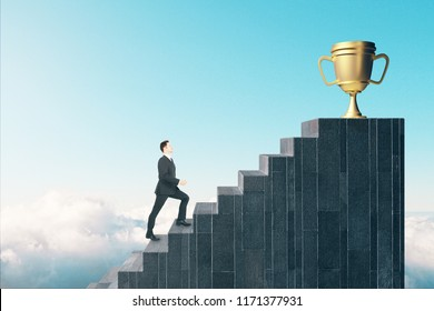 Side view of young businessman climbing stairs to award on sky background. Winner and leadership concept.