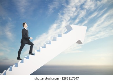 Side view of young businessman climbing abstract stairs arrow on blue sky background. Career promotion and finance concept