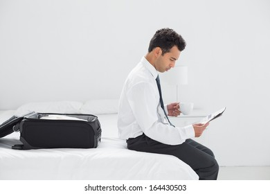 Side view of a young businessman with coffee cup reading newspaper at a hotel room