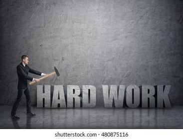 Side view of young businessman crashing 3D concrete 'hard work' words with a hammer. Efficiency at work. Successful management. Business staff.