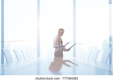 Side view of young businessman with document in hands standing in modern conference room interior with city view and shadow. Worker and boss concept. Double exposure