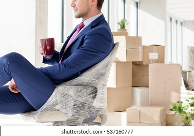 Side view of young businessman having coffee on chair in new office