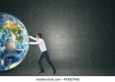 Side view of young businessman pushing the globe against blackboard . Concept of a new business project. Toned image. Mock up
