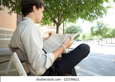 Side view of a young businessman reading a financial newspaper while sitting on a bench in the city, outdoors.