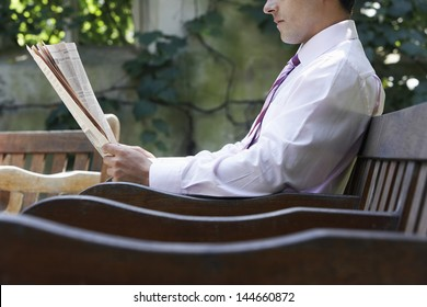 Side view of young businessman reading newspaper on park bench