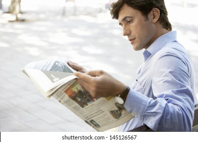Side view of young businessman reading newspaper on bench outdoors