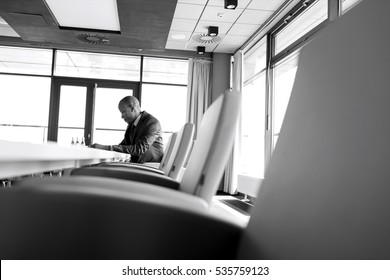 Side view of young businessman sitting at table in board room