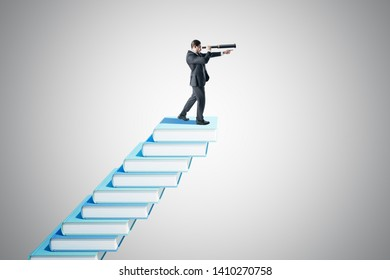 Side view of young businessman with telescope on creative book ladder. Grey background. Growth, knowledge and vision concept