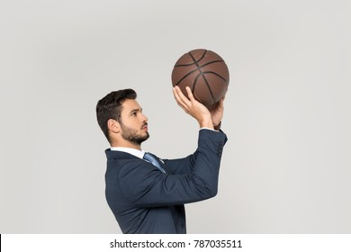 side view of young businessman throwing basketball ball isolated on grey