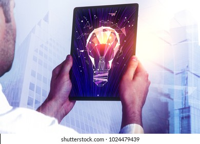 Side view of young businessman using tablet with glowing polygonal lamp on abstract city background. Idea concept. Double exposure