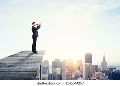 Side view of young businessman using binoculars to look into the distance on city background with copy space. Research and tomorrow concept