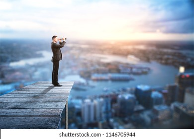Side view of young businessman using binoculars to look into the distance on city background with copy space. Research and job search concept