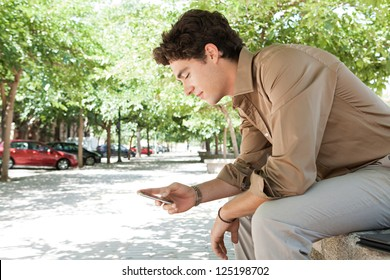 Side view of a young businessman using his smart phone while sitting on a ben in a city park, outdoors.