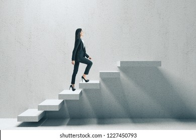 Side view of young businesswoman climbing concrete stairs. Career development and success concept.