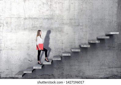 Side view of young businesswoman climbing the stairs on concrete background