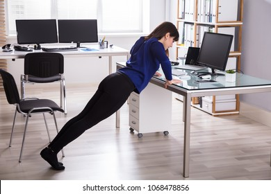 Side View Of A Young Businesswoman Doing Push Up On Office Desk
