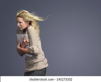 Side view of a young businesswoman with folder and blond hair blowing in wind against gray background