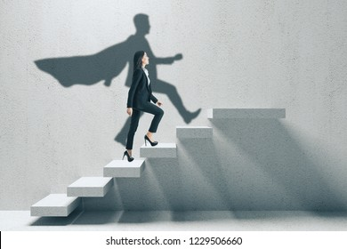 Side view of young businesswoman with hero shadow climbing concrete stairs. Career development and confidence concept.