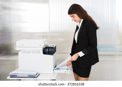 Side view of young businesswoman inserting papers in photocopy machine at office
