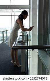 Side view of young businesswoman leaned on the railing and chating on his mobile phone on first floor walkway against end of the walkway in background