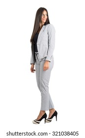 Side view of young businesswoman looking behind over the shoulder.  Full body length portrait isolated over white studio background.