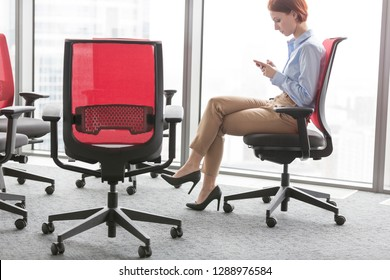 Side view of young businesswoman messaging on smartphone while sitting on red seat at office