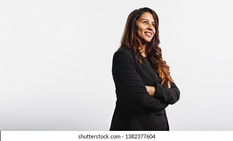 Side view of young businesswoman standing against white background and looking away. Portrait of smiling businesswoman having golden brown hair.