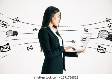 Side view of young businesswoman using laptop with communication sketch on white background. Social network and media concept