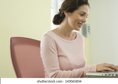 Side view of young businesswoman using laptop in conference room