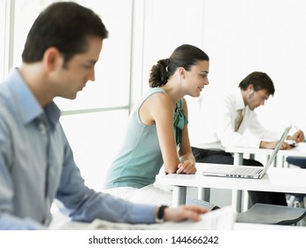 Side view of young businesswoman using laptop with male colleagues working in office