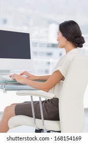 Side view of a young businesswoman using computer in a bright office