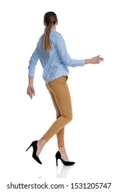side view of young businesswoman wearing blue shirt and looking to side, walking isolated on white background