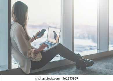 Side view of young businesswoman in white shirt sitting on floor near window and uses laptop and smartphone. In background is blurred cityscape. Student learning online.Girl shopping online, blogging.