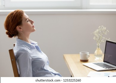 Side view young calm female sitting at office desk in workplace opposite computer with closed eyes daydreaming breathing fresh air. Finishing work satisfied businesswoman resting relaxing feels good