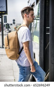 Side view of young casual dressed man with backpack walking into bus.